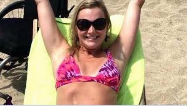 Młoda kobieta jest szczęśliwa na plaży, gdy jednak zobaczysz jej pełne...
