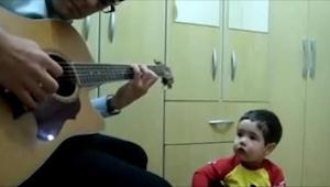 Dziecko patrzy na swojego tatę, który trzyma gitarę. Nie mogę uwierzyć w to, co