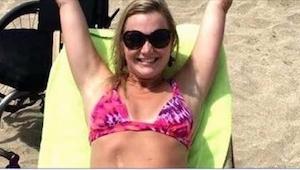 Młoda kobieta jest szczęśliwa na plaży, gdy jednak zobaczysz jej pełne zdjęcie,