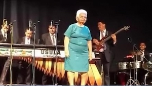 Starsza pani w niebieskiej sukience wychodzi na środek sceny. To, co robi już w