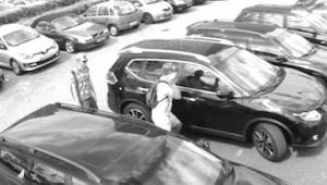Mężczyźni zaglądają do samochodu i wydają się go okradać. Prawdziwy powód właman