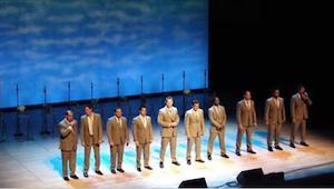 Grupa mężczyzn wychodzi na scenę. Po chwili śmiechom i gwizdom publiczności nie