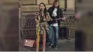 Dziewczyna ubrana w zalotną sukienkę i wysokie obcasy zbliżyła się do ulicznego