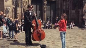 Mała dziewczynka gra na flecie dla wiolonczelisty, chwilę później wszyscy widzow