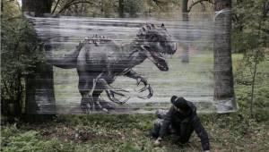 Artysta robi graffiti na kawałku folii rozwiniętej w lesie. Oto efekt