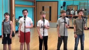 5 chłopców ustawia się by zaśpiewać swoją wersję piosenki ze znanego musicalu. T