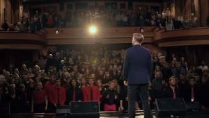 Piosenkarz stoi przed chórem 200 młodych ludzi. Posłuchajcie tej wspaniałej wers